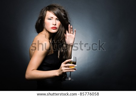 Beautiful sexy woman with a glass of white wine on a dark background.