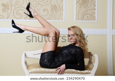 beautiful sexy woman with blond hair in elegant black dress - stock photo