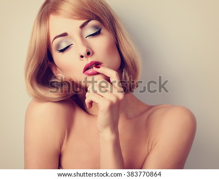 Beautiful sexy woman with bright eyes makeup touching her lips with desire. Toned closeup portrait