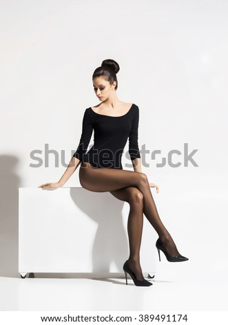 Beautiful, sexy woman with hot legs sitting on cube over isolated background. - stock photo