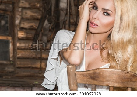 Beautiful sexy woman with long curly blond hair, green eyes pretty sweet and sexy full lips on the wild west - stock photo