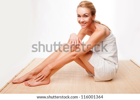 Beautiful sexy woman with long shapely legs relaxing in a towel on a reed mat in a health and beauty concept, isolated on white - stock photo