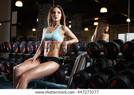 beautiful sexy woman with perfect abdominal muscles at the gym