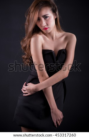 Beautiful sexy woman with perfect slim body and long curly hair in black dress posing over black background. Studio shot.