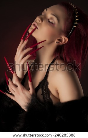 Beautiful sexy woman with red hair and long nails in fur coat and golden spike crown - stock photo