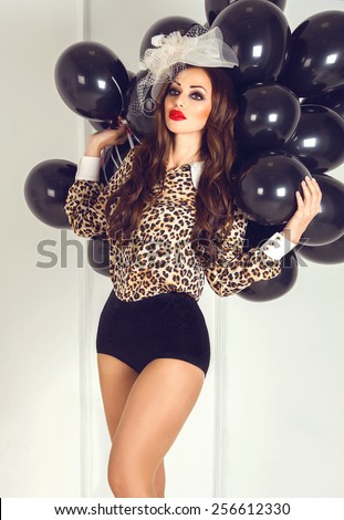 Beautiful sexy woman with red plump lips in retro hat and black vintage panties with black balloons in her hands posing like a doll on bright background - stock photo