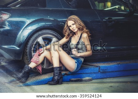 Beautiful sexy woman working to repair the car in the showroom, the style of fashion photography on the background of wheels and tires