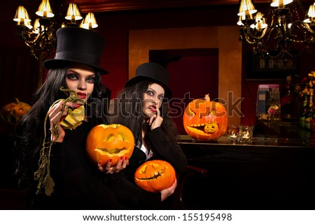 Beautiful sexy women with halloween pumpkins over red background - stock photo