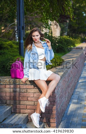 Beautiful sexy young blonde woman with long wavy hair thin slender figure perfect body and pretty face make-up wearing in a white vintage suit and a blue jeans jacket . summer accessory,pink backpack