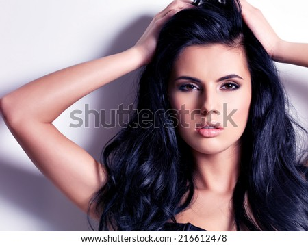 Beautiful sexy  young brunette woman with long  hair.  Portrait of a pretty fashion model posing at studio. - stock photo