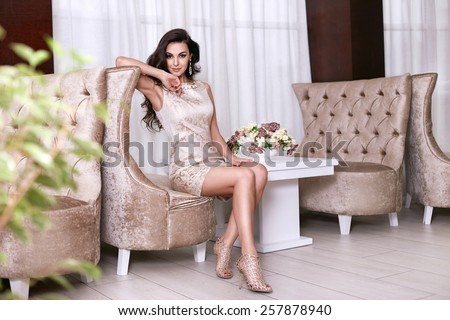 Beautiful sexy young brunette woman with long wavy hair thin slender figure perfect body and pretty face make-up wearing a beige evening skinny dress and jewelry. - stock photo