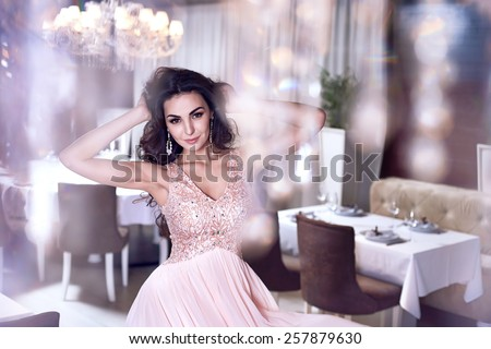 Beautiful sexy young brunette woman with long wavy hair thin slender figure perfect body and pretty face make-up wearing a pink evening skinny dress and jewelry  - stock photo