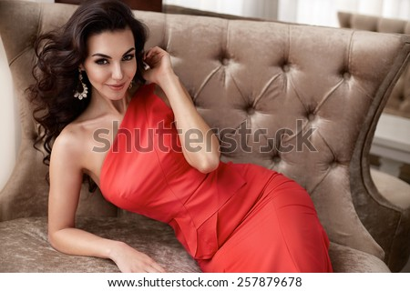 Beautiful sexy young brunette woman with long wavy hair thin slender figure perfect body and pretty face make-up wearing a red evening skinny dress and jewelry  - stock photo