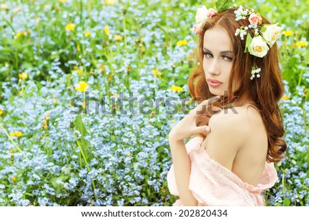 beautiful sexy young girl with long red hair with flowers in her hair, sitting in a field in blue flowers