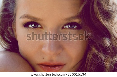 Beautiful sexy young woman evening make up dark eye eyelashes dyed brunette waves stacked hair nude shoulder Golden Tan looks into the camera from the back - stock photo