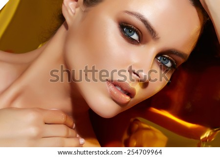 Beautiful sexy young woman evening make up dark eye eyelashes dyed brunette waves stacked hair nude shoulder Golden Tan looks into the camera makeup artist cosmetic beauty salon spa - stock photo