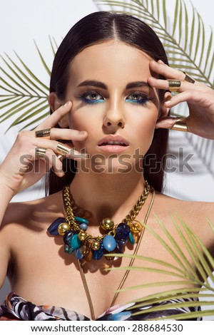 Beautiful sexy young woman evening make up. Eyelashes dyed brunette waves stacked hair. Golden skin tan looks into the camera. Cosmetic beauty salon spa. Summer look. Tropical style, wet hair - stock photo