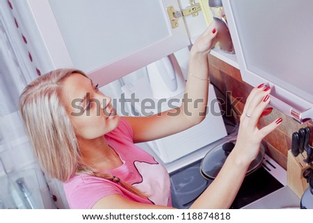 beautiful sexy young woman getting out of the cupboard a jar - stock photo