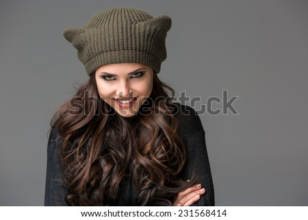 Beautiful sexy young woman in a  funny hat with ears smiling on gray background - stock photo