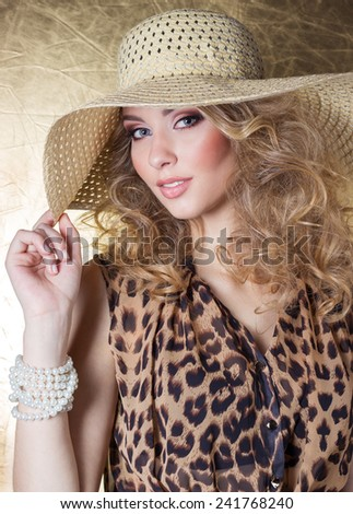 beautiful sexy young woman in dress leopard bright makeup in the Studio on a gold background in the hat - stock photo