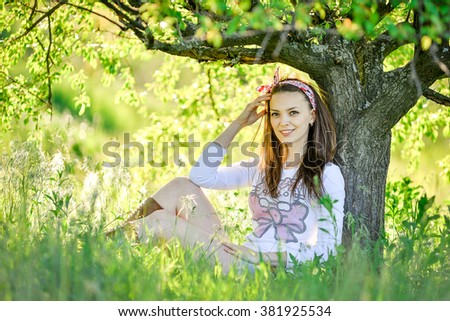 beautiful sexy young woman is sitting on the grass in the garden