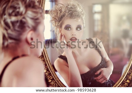 Beautiful sexy young woman near a mirror - stock photo
