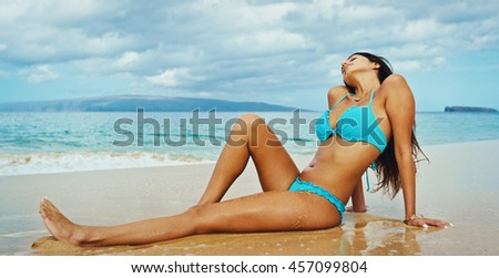 Beautiful sexy young woman relaxing on the beach - stock photo