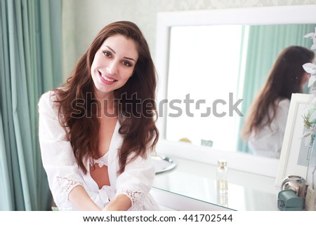 Beautiful sexy young woman sitting near the mirror at her bedroom smiling to camera - stock photo