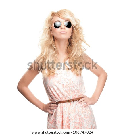 Beautiful sexy young woman standing isolated on white background. Looking into the camera and wearing sunglasses. Long wavy blonde hair. - stock photo