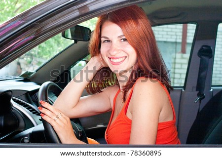 beautiful sexy young woman with red hair is driving a car