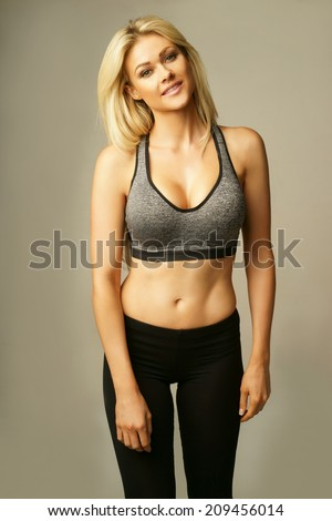 Beautiful shapely curvy young blond woman in sexy sportswear with a bare midriff and sports bra accentuating her full breasts holding her hand to her hair smiling seductively at the camera, on grey - stock photo