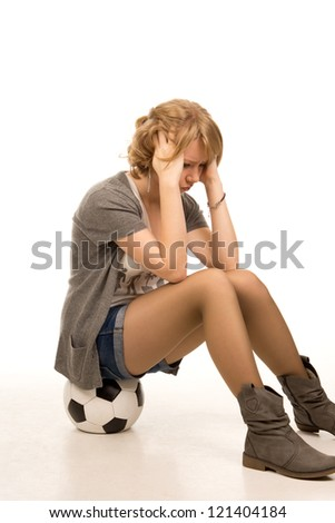 Beautiful shapely dejected young woman dressed in trendy shorts sitting with her head in her hands on a soccerball, side view full body portrait isolated on white - stock photo