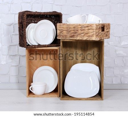 Beautiful shelves and boxes with tableware  on  light wall background - stock photo