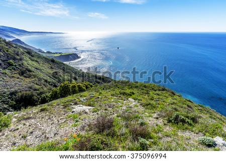 Beautiful shimmering  blue sea, aquamarine ocean, and white puffy clouds, along steep sheer jagged cliffs, near Carmel, CA. traveling the Big Sur Highway (Highway 1), on the California Central Coast. - stock photo