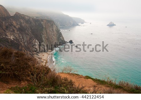 Beautiful shimmering blue sea, ocean, and white puffy clouds, along steep sheer jagged cliffs - stock photo