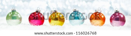 Beautiful shiny Christmas ball banner arranged in a row on fresh white winter snow with a backdrop of sparkling lights - stock photo