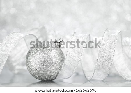 Beautiful shiny Christmas ball decoration on silver background