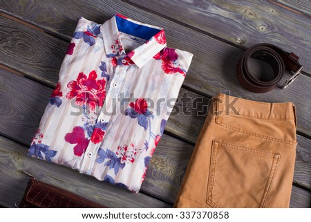 Beautiful shirt with accessories on a wooden background. - stock photo