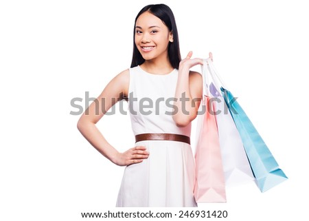 Beautiful shopaholic. Beautiful young Asian woman in pretty dress looking at camera and holding shopping bags while standing against white background   - stock photo