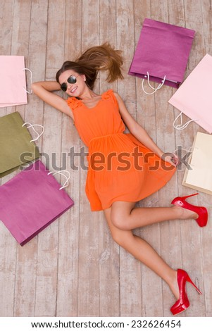 Beautiful shopaholic. Top view of beautiful young woman in sunglasses holding hand in hair and smiling while lying on the floor among shopping bags   - stock photo