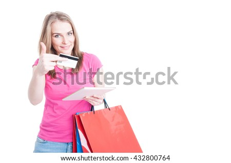 Beautiful shopper buying things or doing online shopping with tablet pc and credit card and showing thumbup isolated on white with copyspace
