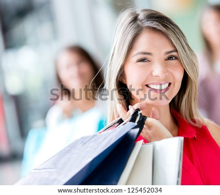 Beautiful shopping girl holding bags and smiling