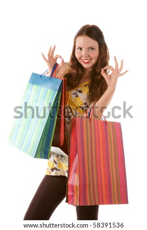 Beautiful shopping girl with bags indicating OK sign - stock photo