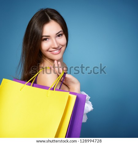 beautiful shopping girl with vivid colored sale bags over blue background - stock photo