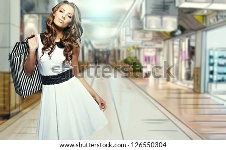 Beautiful shopping woman at a mall smiling - stock photo