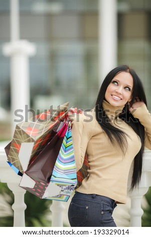 Beautiful shopping woman happy holding shopping bags outdoor. Walking in the street - stock photo