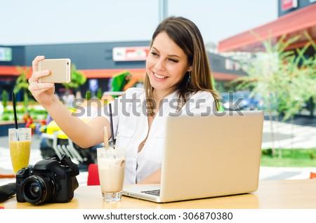 Beautiful shopping woman taking selfie at the shopping mall - stock photo