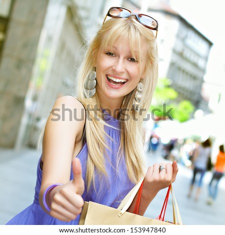 Beautiful shopping woman with bags show approved sign by hand in the city.