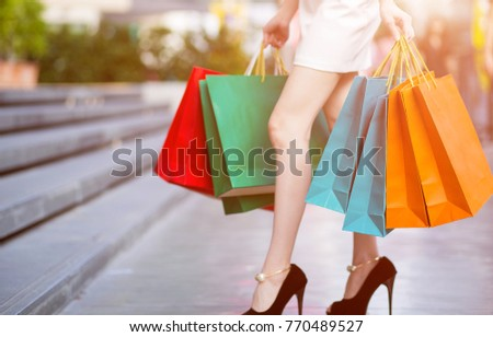 Beautiful Shopping woman with colorful shopping bags walking in the city.