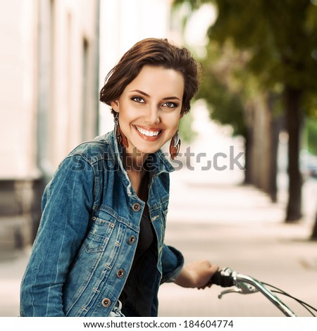 beautiful short haired young girl in denim jacket on a bike smiles for the camera - stock photo